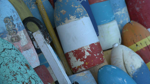 Close-up pan of striped fishing buoys stacked in Massachusetts Footage