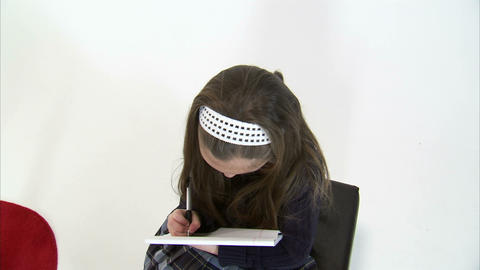 Royalty Free Stock Footage of Move above a girl doing homework on white Live Action