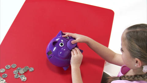 Royalty Free Stock Footage of Young girl putting a coin in a purple piggy bank Footage