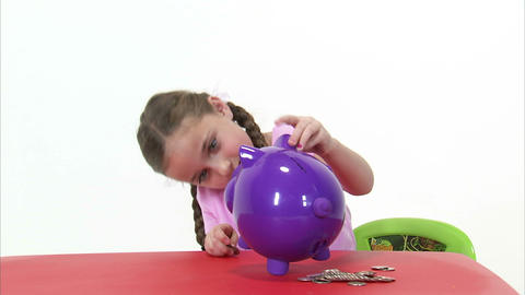 Royalty Free Stock Footage of Young girl putting coins in a purple piggy bank on Footage