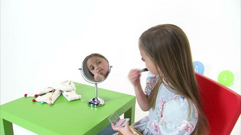 Royalty Free Stock Footage of Young girl putting blush on her cheeks Live Action