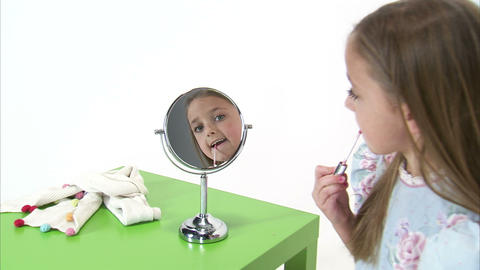 Royalty Free Stock Footage of Young girl putting lip gloss on her lips Footage