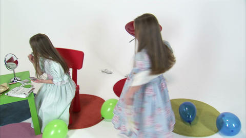 Royalty Free Stock Footage of Young twins, one spinning, one applying makeup Footage