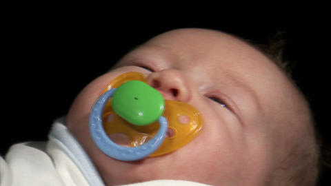 Shot of a pacifier being placed in a baby's mouth Footage