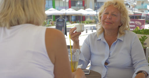 Senior female friends talking in street cafe Footage