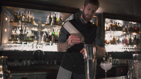 Hipster bartender mixologist combining ingredients and for preparing alcohol Live Action