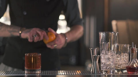 Unrecognizable bartender cuts off the orange zest to make a refreshing alcoholic Footage