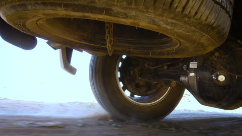 Rear wheel of SUV truck spinning and move on off road terrain with dusk dirty Live Action