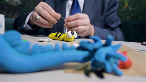 closeup man makes plasticine stripes for toy bee at table Footage