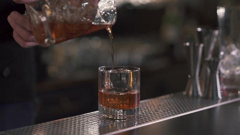 Bartender pouring a refreshing whiskey or alcohol cocktail into a glass with ice Footage