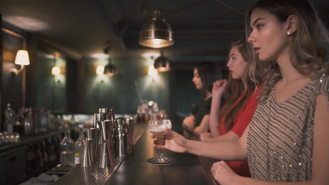 Three upset and angry young girls sit by the bar and drink cocktails one by one Footage