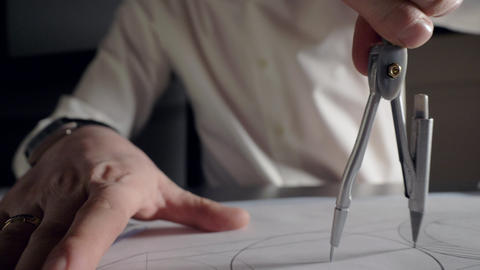 skilled worker draws circle with compass on project drawing Live Action