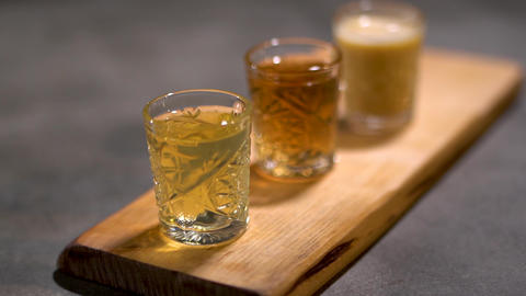 Three alcoholic aromatic shots beautifully serving stay on the wood desk ready Live Action