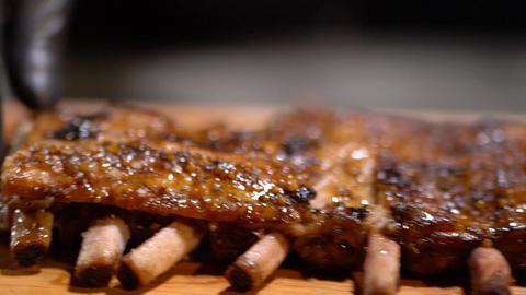 Just cooked juicy fragrant fried ribs throw on the elegant serving wooden table Live Action