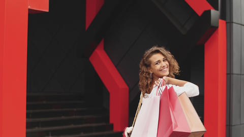 Beautiful woman holding shopping bags and smiling. shopping center background Footage