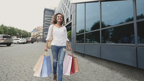 woman holding shopping bags and enjoying the commercial store sales. Successful Live Action
