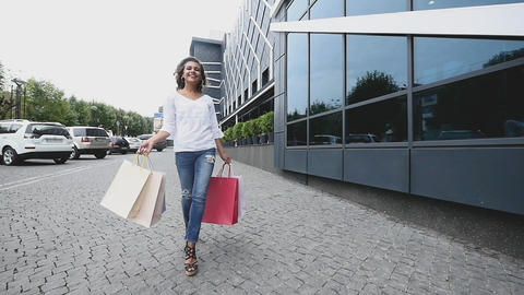 Beautiful girl with packages after shopping. Girl walking around the city after Footage