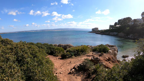 Walking on a dirt path to the beach in Alghero shoreline Live Action