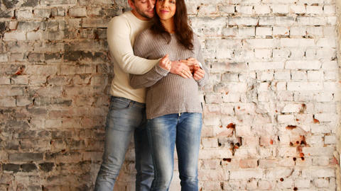 Mom and dad hands on pregnant tummy showing heart sign. Pregnant couple Archivo