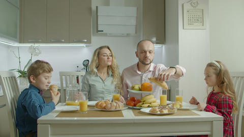 Pleasant happy family having morning meal together Live Action