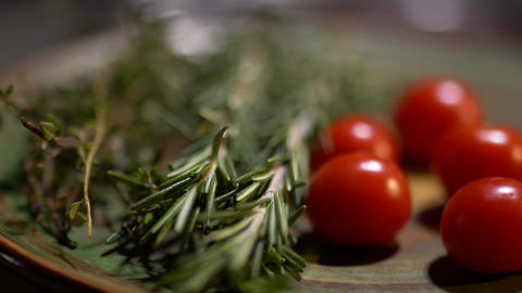 Fresh rosemary and tasty juicy red tomatoes lying on the kitchen board closeup Footage