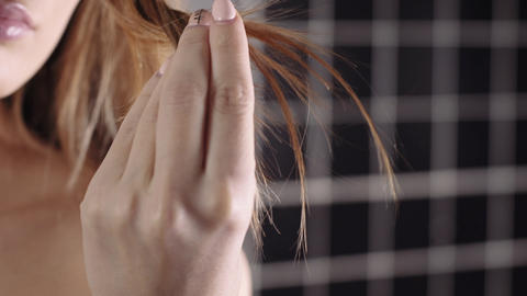 Woman holds her dry brittle hair in a hand, hair care, shampoo and cosmetics for Live Action