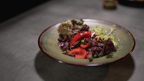 Salad ingredients fall in the plate standing on the table surface. Food Live Action