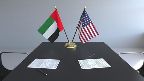 Flags of the United Arab Emirates and the United States and papers on the table Live Action