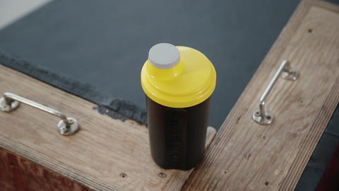 Sportswoman take bottle with sports nutrition and putit on bench. Close up with Live Action