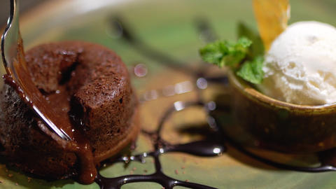 Brown sweet filling follows from the cake lying on the plate close up Footage