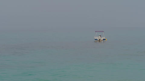 Small motor boat at anchor sways on gentle waves of blue sea Live Action