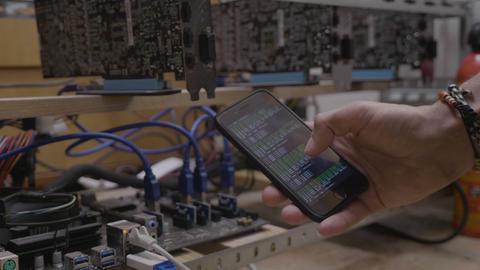 Technician man showing mining software progress on smartphone display near the Footage