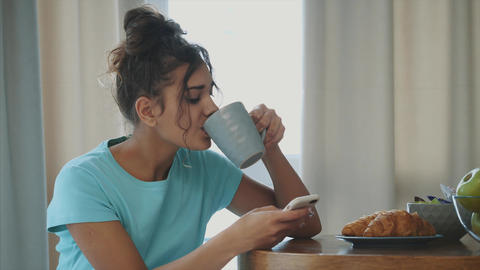 Young Happy Woman Refreshing with Cup of Coffee, Snacks and Fresh Fruit at the Footage