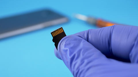 Technician worker holding micro SD card in repairing service center Live Action