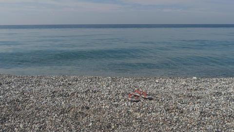 Smooth pebbles in clear azure sea waves. Pair of flip-flops on a seashore. Slow Footage