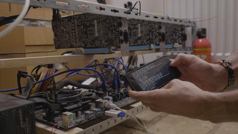 Trader man holding his smartphone near the gpu cryptocurrency mining rig with Live Action