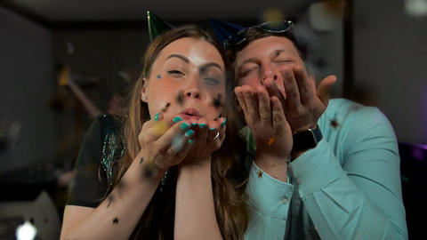 Young couple having fun at party, wear party hats, blowing party confetti Live Action