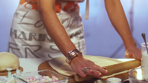 Woman in apron rolls out dough on round shaped wooden board with rolling pin Live Action