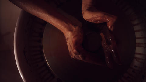 Women's hands are working on pottery wheel shaping brown thin clay pot Footage
