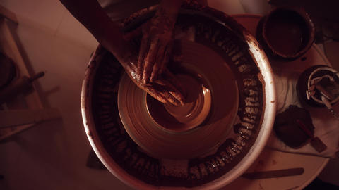 Top view of potter's wheel with tray table and hands shaping small clay plate Footage