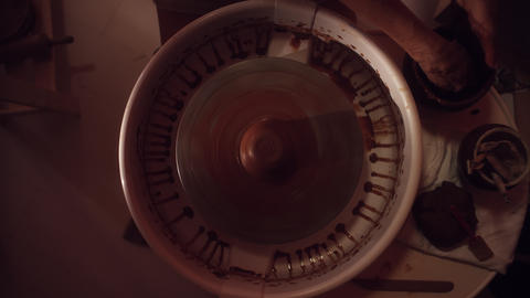 Women's hands are working on potter's wheel shaping long thin clay pot Footage