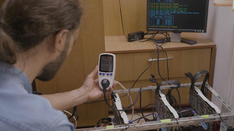 Expert technician using a power meter monitoring and indicating consumption and Live Action