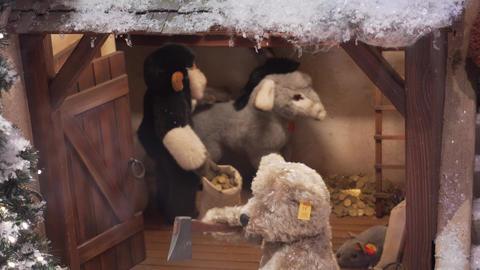 MUNICH, GERMANY - NOV 20, 2018: A mechanical toy bear cuts a log, a monkey Footage