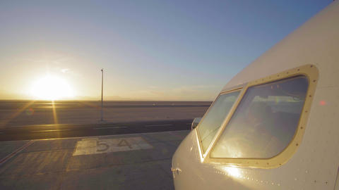 Jet plane in airport runway as silhouette in front of large sunset 4K UltraHD Live Action