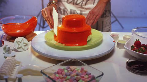 Small double decker cake covered by orange cream is being slowly smoothed Footage