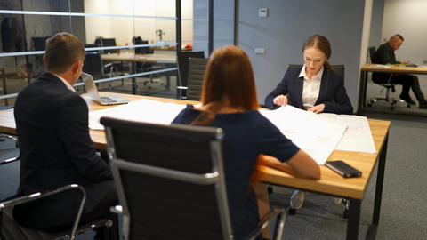 Confident businesspeople giving drawing presentation on drawings to colleagues Live Action