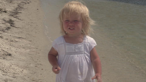 Beautiful little girl walks along the seashore. Laughing baby. Little girl in a Live Action