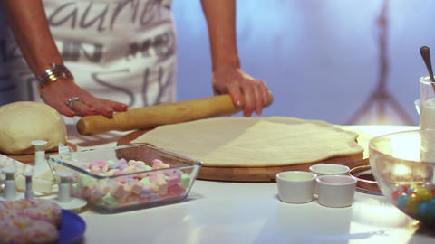Woman's hands with bracelets and rings roll out dough on board with rolling pin Live Action