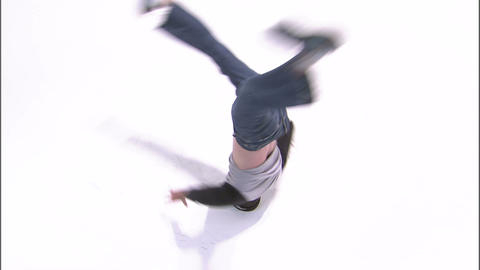Overhead shot of a break dancer doing a head spin on a white background Footage