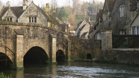 Tilt from a stone bridge over a stream to a stone village in England Footage